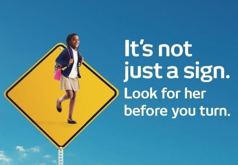 Yellow traffic sign with photo of girl with backpack with phrase: It's not just a sign,. Look for her before you turn.""