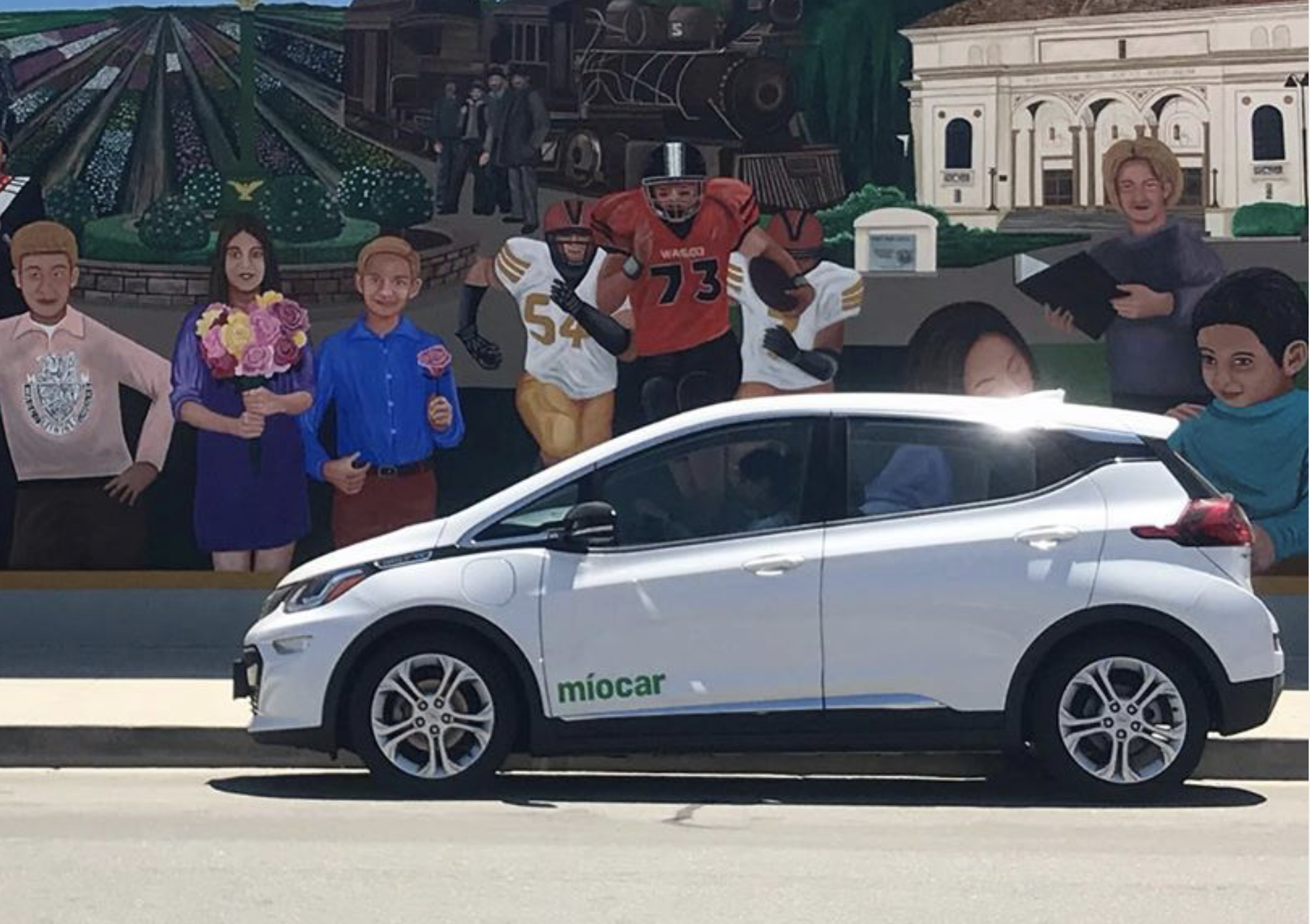 Miocar parks in front of mural in Wasco